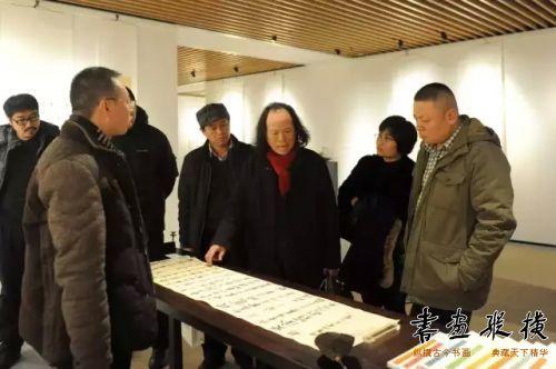 中国国家画院沈鹏工作室助教张德林同参展作者观看展览